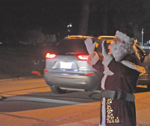 "Christmas Parade, Dec. 9: Last year's annual Lighted Christmas Parade, hosted by the Sulphur Springs Lions Club, was a little different as cars drove past stationary floats in a ""drive-thru style."" Above, Santa Claus himself waves to the cars passing by. File photo by Todd Kleiboer"