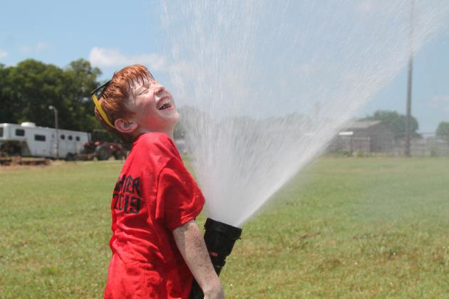 Zach Mansfield turns the hose on himself at Arbala Junior Firefighter Academy this past weekend which 45 kids attended. See more photos on page 12A. Staff Photo by Taylor Nye