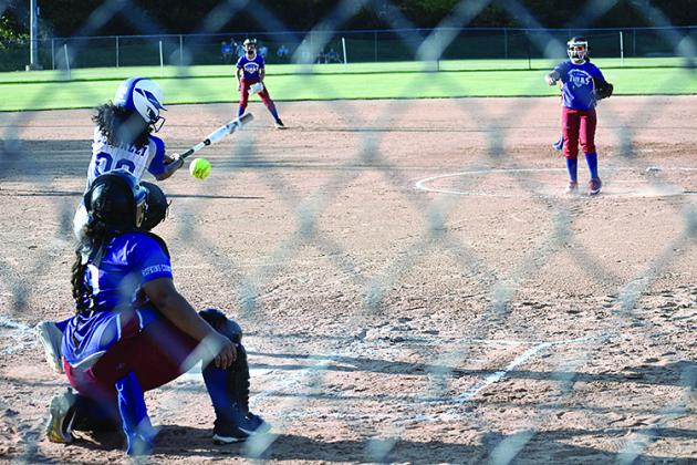 Hopkins County's Lucy Hernandez (left) prepares to snag a pitch from Hannah Speed (right) after a missed swing from Alabama's Harmoni Descalzi during game one of the championship series. The Hopkins County Ponytails finished second in the nation, while the county's Debs, Angels and Sweetees teams all finished third. The Ponytails, Debs and Angels all finished top three as the host team while the Sweetees were the state champions.