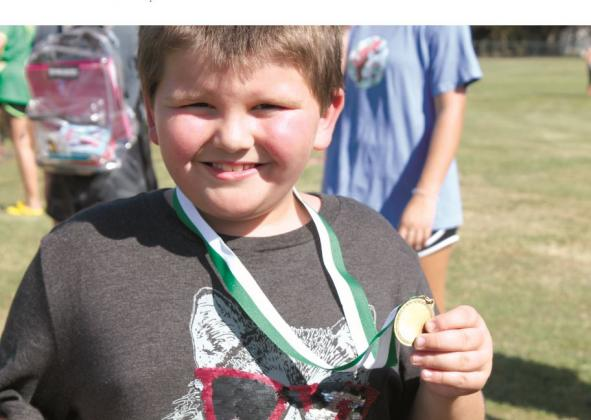 Mason Nalls, a Miller Grove second grader, proudly shows off his fun run medal. The school hosted the Miller Grove Invitational Cross Country meet on Thursday, Sept. 12, and elementary school students participated in their own race as part of the activities. Staff photo by Taylor Nye