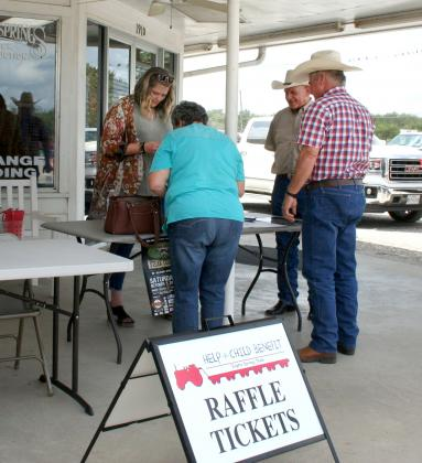 Dwyatt Bell (second from right), chief operating officer of NETBIO, and Rebecca McDaniel (left) were busy selling meal and raffle tickets for the upcoming NETBIO Steak Cookout slated for Saturday, Oct. 5.