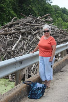 Texas State Highway 71 advocate Marna Martinez poses in front of the log jam at the bridge. Courtesy