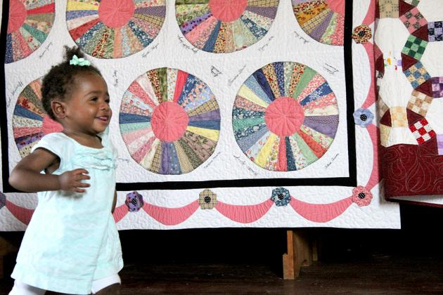 A young girl plays in the church at Heritage Park among the quilts displayed along the walls.