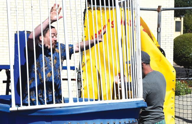 Brad Cummings (left), Precinct 2 Justice of the Peace, is dunked into the tank as event organizer Clay Pirtle helps the ball thrower hit the target. According to Pirtle, 110 people preregistered for the event, and several registered at the event. Staff photo by Todd Kleiboer
