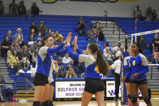 Sadie Washburn (left) and Peyton Hammack exchange high fives following a big point during recent home volleyball action. The Lady Cats will host rival Texas High Tuesday. Senior night activities begin at 6 p.m. for the Lady Cats. Photo by Don Wallace