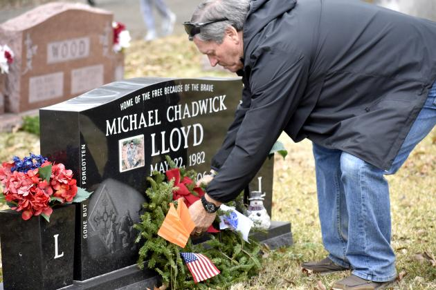 Jimmy Lloyd, husband of organizer Dena Lloyd, sets an evergreen wreath at the grave of their son, Michael Lloyd, at the Wreaths Across America wreath-laying event in Sulphur Springs' City Cemetery Saturday morning. The nation-wide event honors the sacrifice and service of deceased U.S. military veterans. This year, Dena Lloyd raised funding for more than 700 wreaths to place in City Cemetery and Mel Haven Cemetery. Staff photo by Jillian Smith