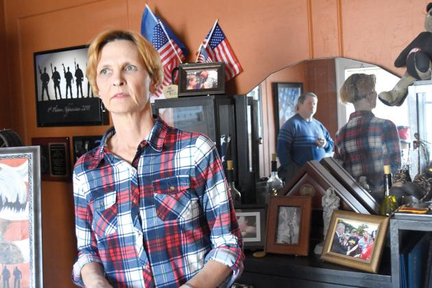 Patti Sells, mother of Tanner Stone Higgins, stands in her home office with Jimmy Lloyd and wife Dena (not pictured) surrounded by keepsakes donated to her after her son was killed in action. Staff photo by Jillian Smith