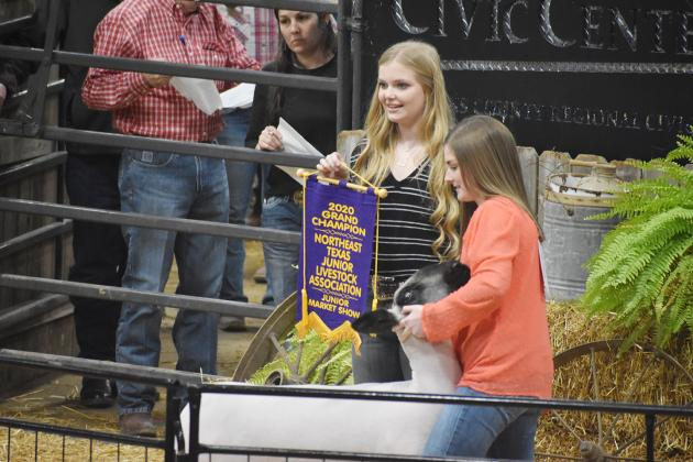 Sulphur Springs FFA member Annie Horton (right) holds her Grand Champion Lamb during the weekend auction of the Northeast Texas Junior Market Livestock Show in the Hopkins County Regional Civic Center. Horton also received Best Showmanship in her class.