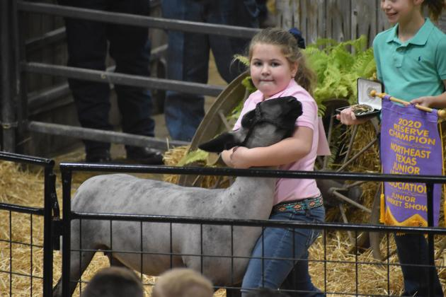 Hopkins County 4-H member Ryan Ragan holds her Reserve Champion lamb Saturday during the Northeast Texas Junior Market Livestock Show at the Hopkins County Regional Civic Center.