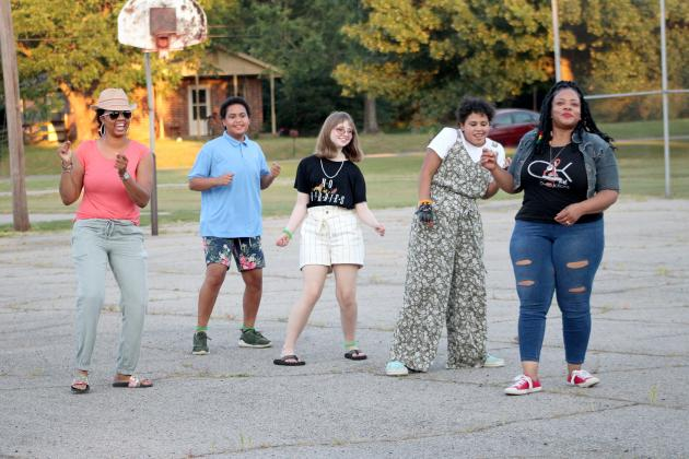 Attendees of the Juneteenth celebration at Pacific Park Thursday evening danced on the basketball court , led by event co-organizer Kenya Chaffer (far right). Chaffer and husband Charles also provided much of the live entertainment throughout the evening.