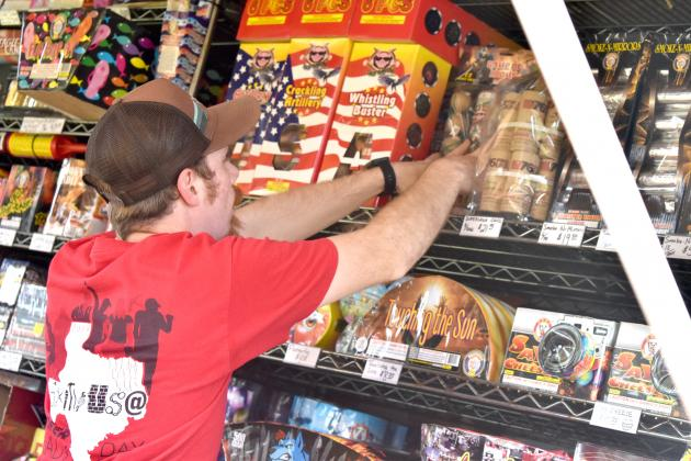 Ruston Pennington checks the stock Wednesday afternoon at the 154 South Fireworks stand. Owner Todd McCoy (not pictured) stressed people should take precautions with their fireworks during the Independence Day holiday. Staff photo by Todd Kleiboer