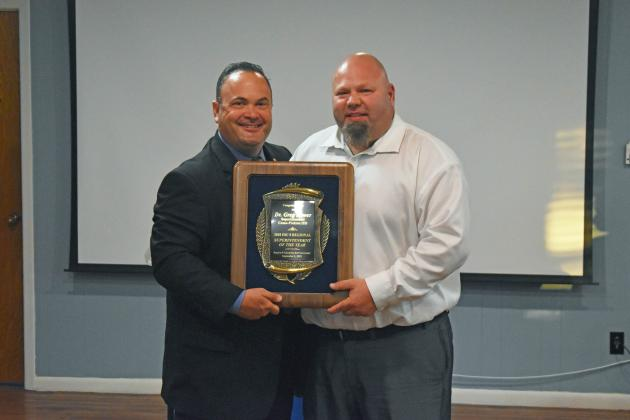 Region 8 Executive Director Dr. David Fitts (left) gives Como-Pickton Consolidated ISD Superintendent Dr. Greg Bower the Region 8 Superintendent of the Year plaque. Staff photo by Todd Kleiboer