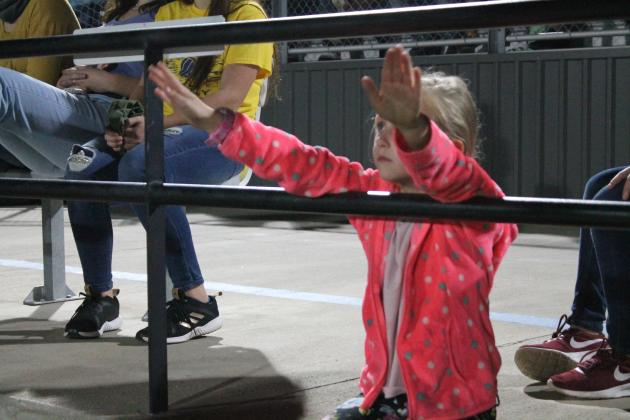 A young fan conducts the band