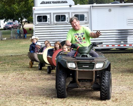 Darris Cross of Como drives little ones around in his barrel train ride on the Hopkins County Civic Center grounds Saturday as part of the Fall Festival. Staff photo by Todd Kleiboer
