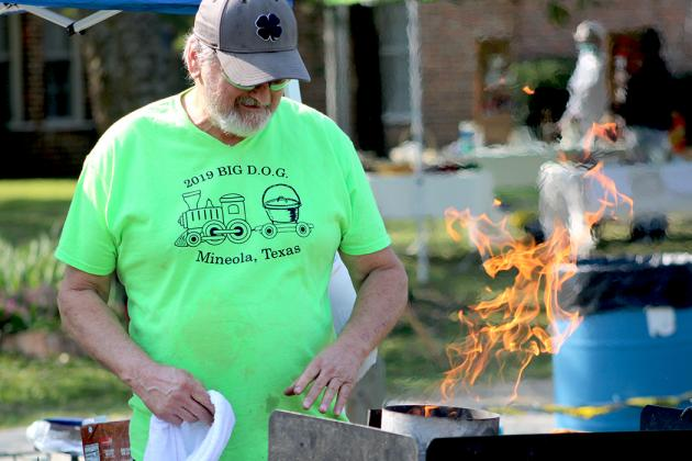 Colley Jones of Mineola fires up his coals in preparation for the annual John Chester Dutch Oven Cook-off held at Heritage Park Saturday with Indian Summer Days. Staff photo by Jillian Smith