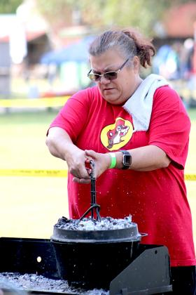 In her 15th year competing at the Johns Chester Dutch Oven Cooking Contest in Heritage Park Saturday, Teresa Reser, of the team Western Gypsies of just outside Tulsa, Okla., gets ready to check one of her entries, lifting the lid and hot coals from the pot. Staff photo by Jillian Smith