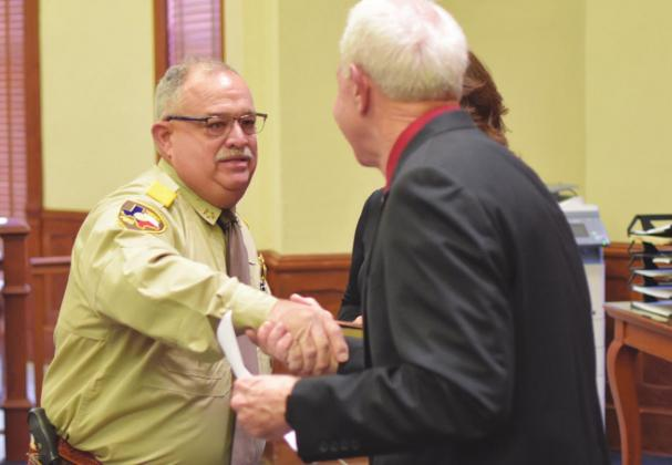 Above: Hopkins County Sheriff Lewis Tatum (left) was sworn in by Hopkins County Judge Robert Newsom (right) Friday and shook hands with him afterward. Tatum was uncontested in his candidacy.