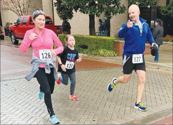 Runners Adrian Childress (left), Shiloh Childress (right) and daughter Madison round the final corner of the race during the Turkey Trot 5K on Thanksgiving Day. Shiloh finished with a time of 23:27 while Adrian finished with a time of 24:09. Staff photos by Taylor Nye